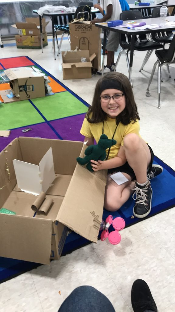 (student Riley proud of her newly constructed Base she created for her Teddy Bear Astronaut)
