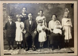 "31Family Photo 1921Roxanne BocyckOnondaga CountyThis photo is of my 18 year old grandmother (standing) along with her brother, his wife, and six children. My grandmother and her brother immigrated from Poland to America in the early 1900s. I am currently writing a novel about her journey from Poland, an arranged marriage, and a possible murder! Or was it self-defense? Either way, I am enjoying the process of ""finding her roots""."