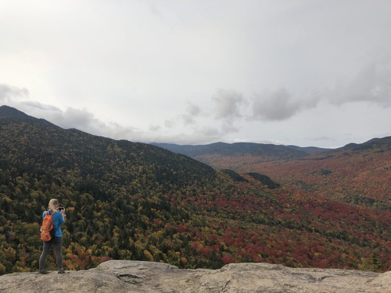 A hiker in the Adirondacks on the top of a summit.